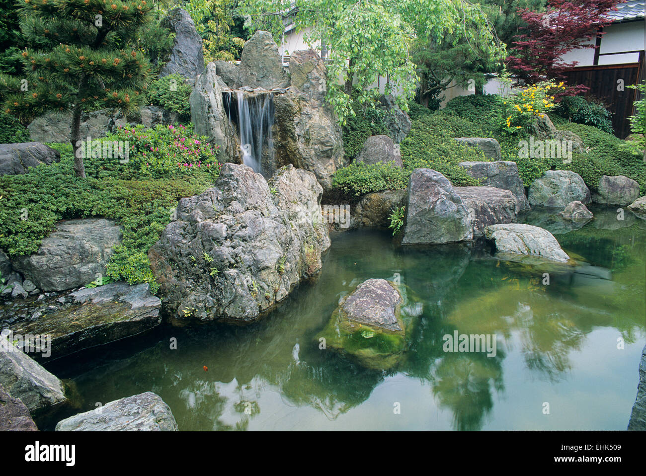 This pond and waterfall exemplifies the simple and natural design of many Japanese gardens. - Stock Image