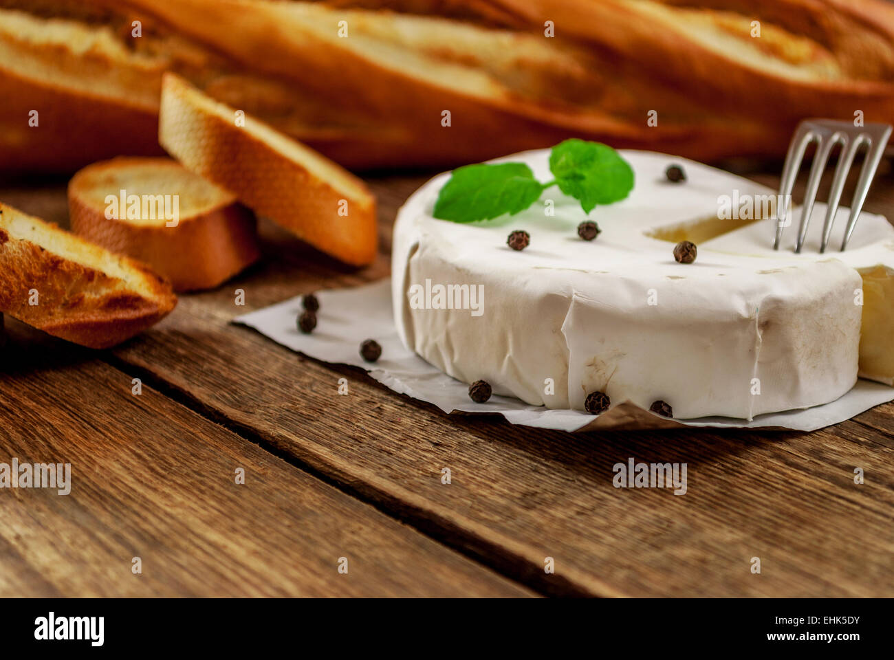 French traditional camembert cheese with baguette on wood table - Stock Image
