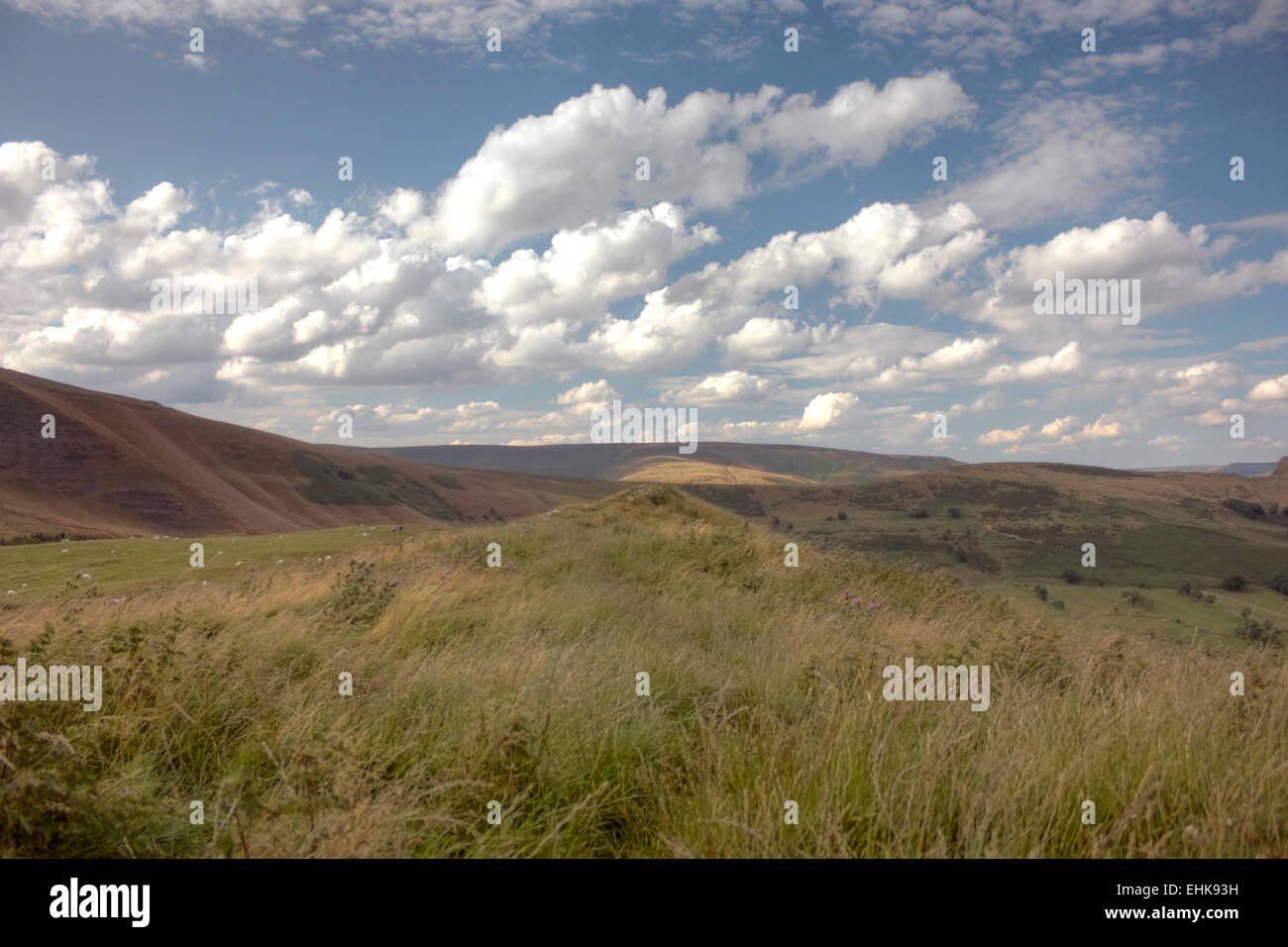 A view of the blue and cloudy sky and distant hills, from the brow of a grassy hill. - Stock Image