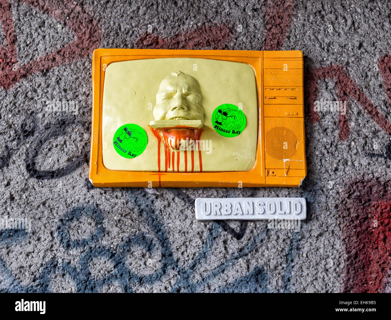 Urban Solid 3-D street art, yellow and orange television screen with protruding head, Mitte, Berlin - Stock Image