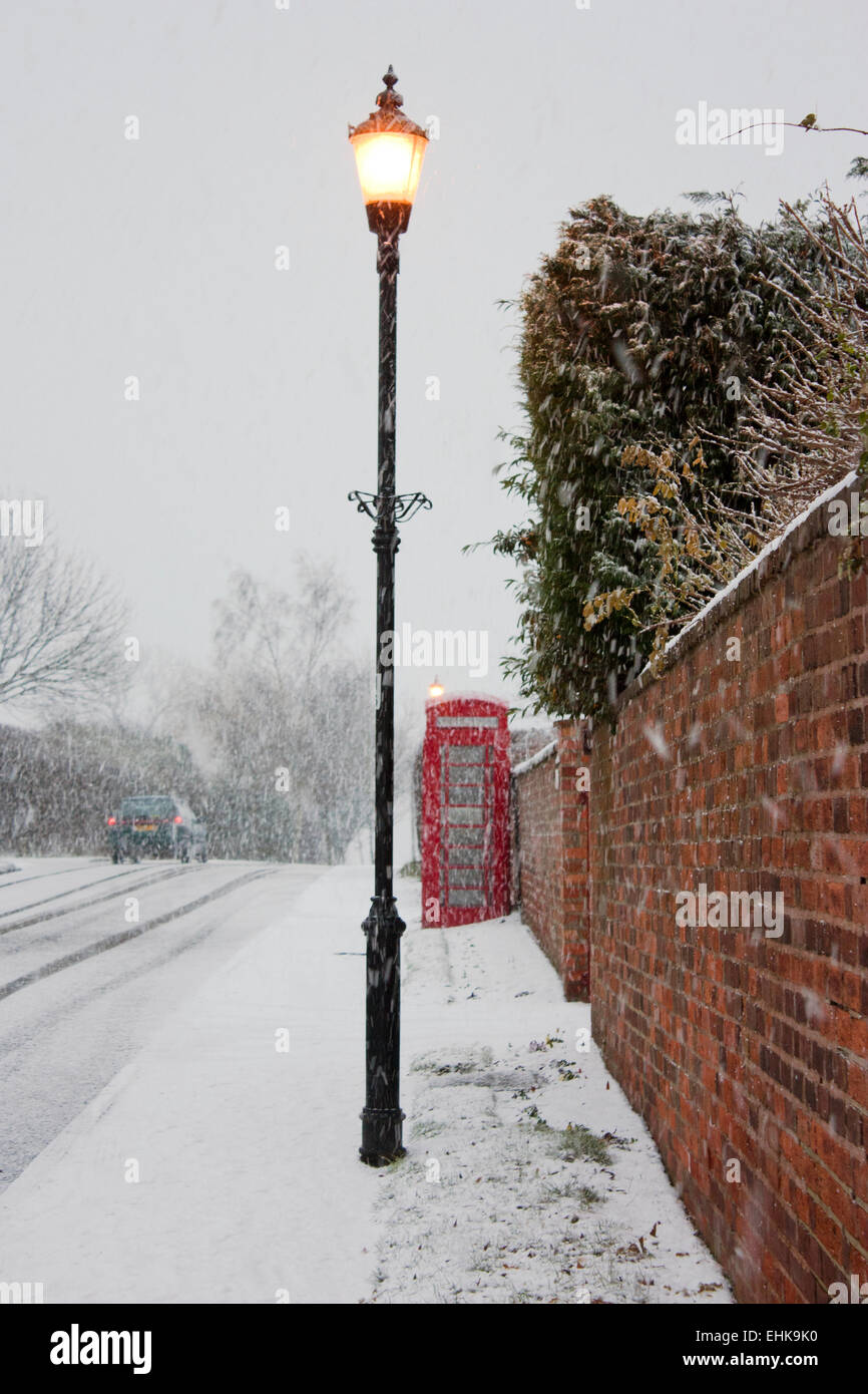 An old red telephone box and an old fashioned lamp post, on a village street covered in snow. - Stock Image