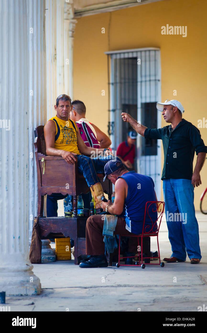 A man shines shoes in Sancti Spiritus, Cuba - Stock Image