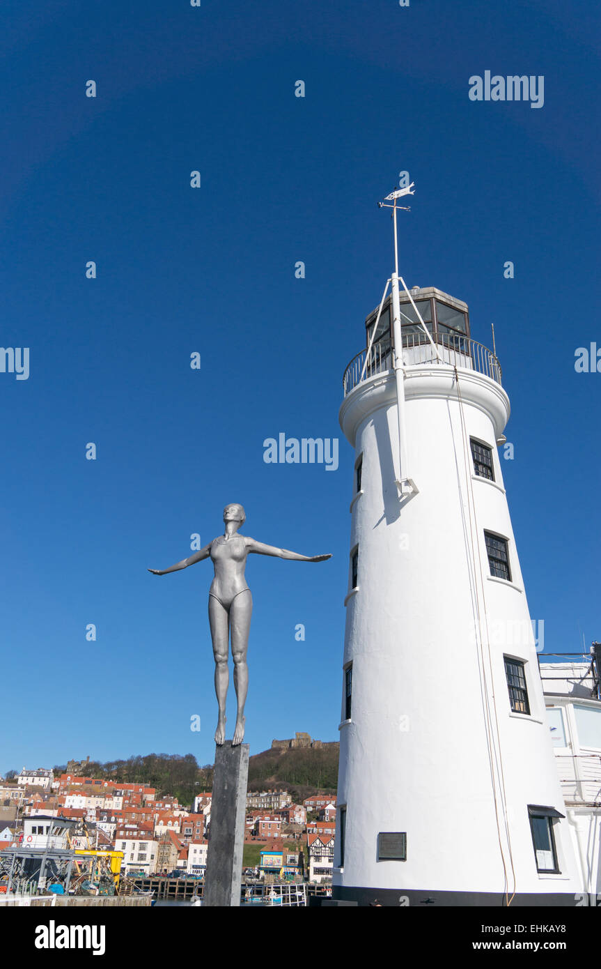The Diving Belle sculpture and lighthouse outside Scarborough harbour, North Yorkshire, UK - Stock Image