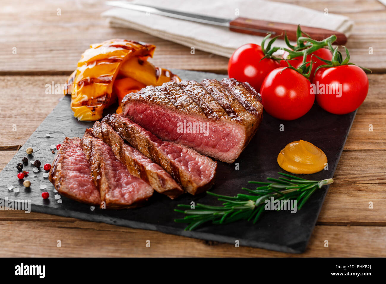 grilled beef steak rare sliced with vegetables - Stock Image