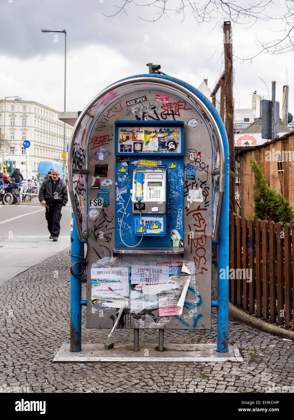 Graffiti covered and dilapidated public telephone box in Berlin street - Stock Image