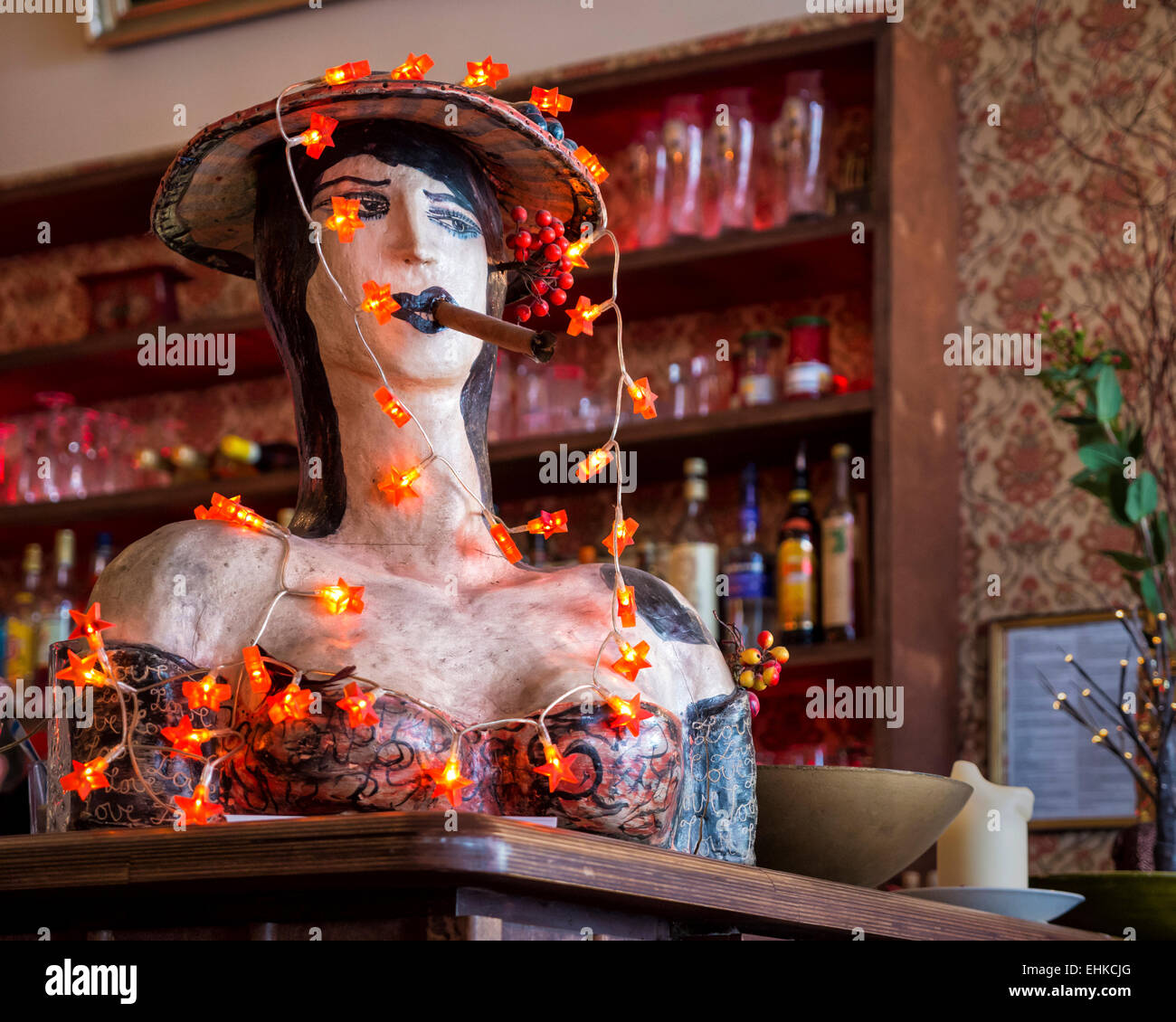 Zur Rose bar and restaurant interior with papier mache bust of woman smoking a cigar and draped in lights, Mitte, - Stock Image