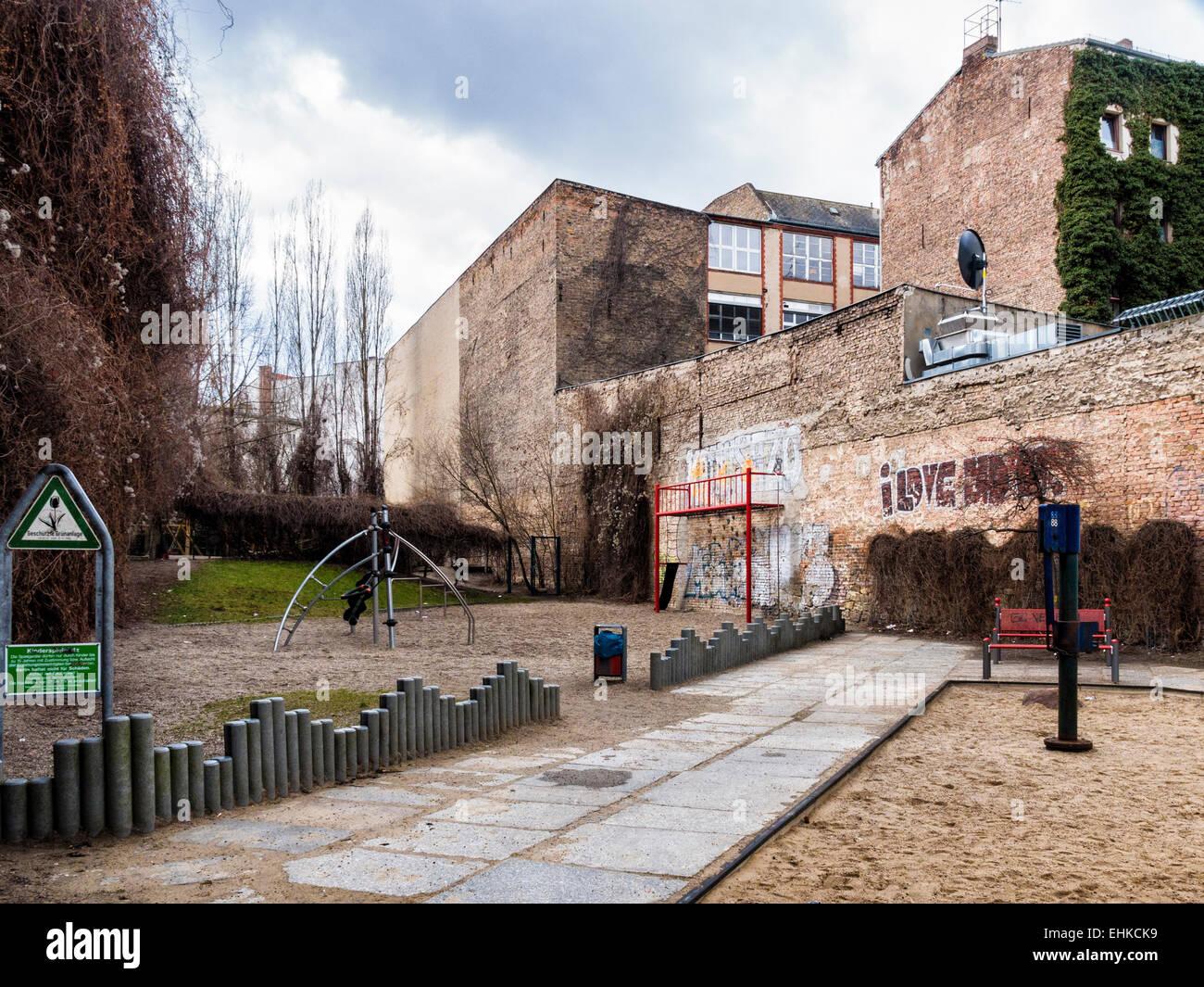 Berlin children's playground surrounded by brick buildings, Kreuzberg, Berlin - Stock Image