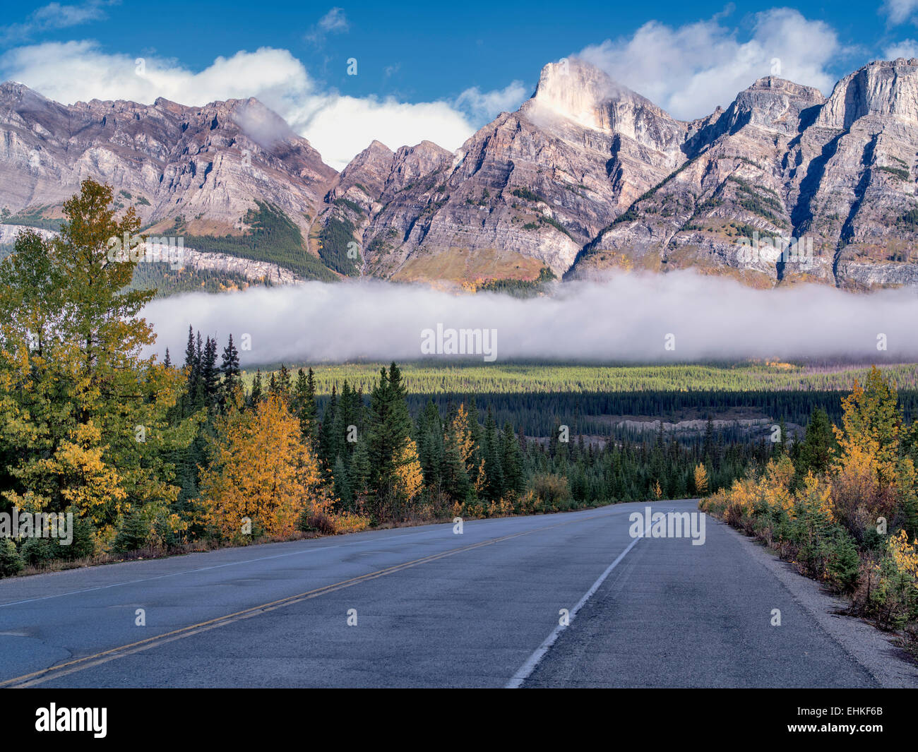 Road, fog and low clouds with autumn colors. Banff National Park. Alberta, Canada Stock Photo