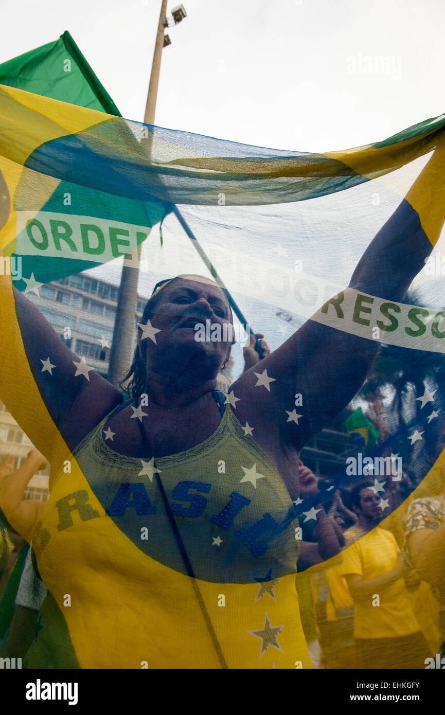 Woman protestor holds a Brazilian flag. Rio de Janeiro, Brazil, 15th March 2015. Demonstration against President - Stock Image