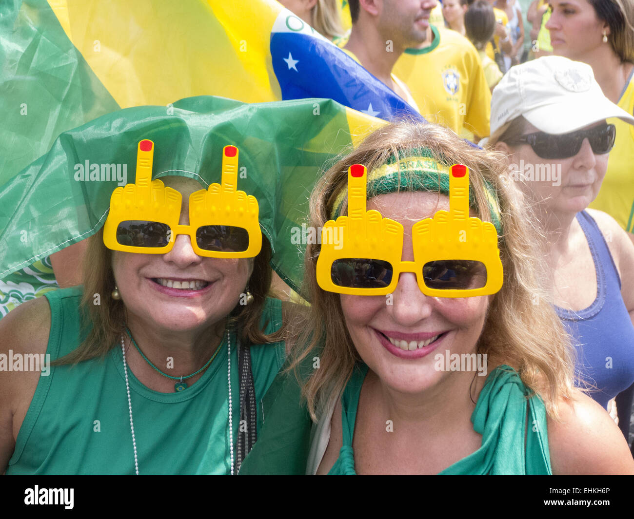 Two youg women wear sunglasses with a middle finger raised in protest. Rio de Janeiro, Brazil. Demonstration against - Stock Image