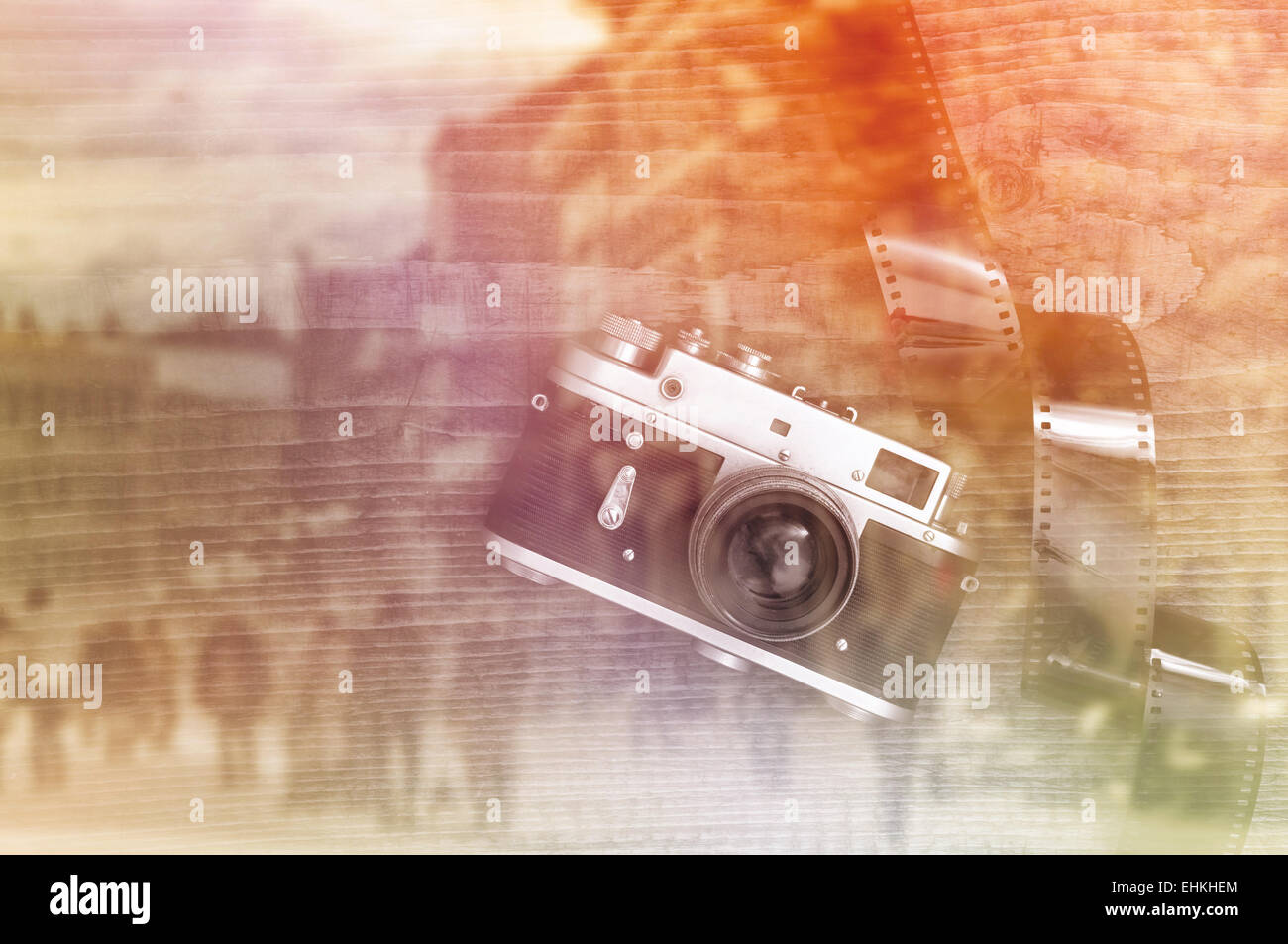 ac0fb1b87af33 Retro style vintage photography camera on a wooden table plate with  overexposed film strip - Stock