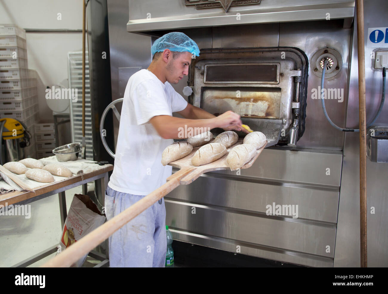 Baker preparing loaves of bread on paddle before placing in the oven - Stock Image