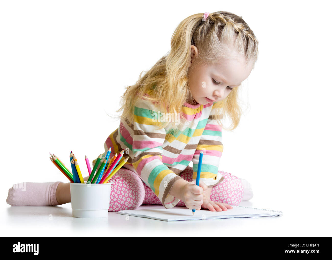 Cheerful child girl drawing with pencils in preschool - Stock Image