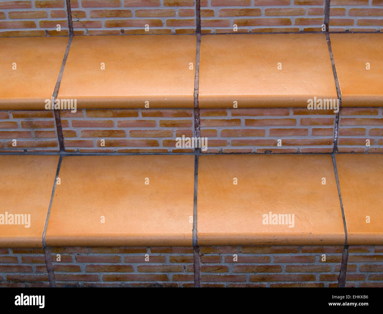 Orange tiles and red bricks, close up of stairs typical for outdoor pedestrian areas in the Canary Islands - Stock Image