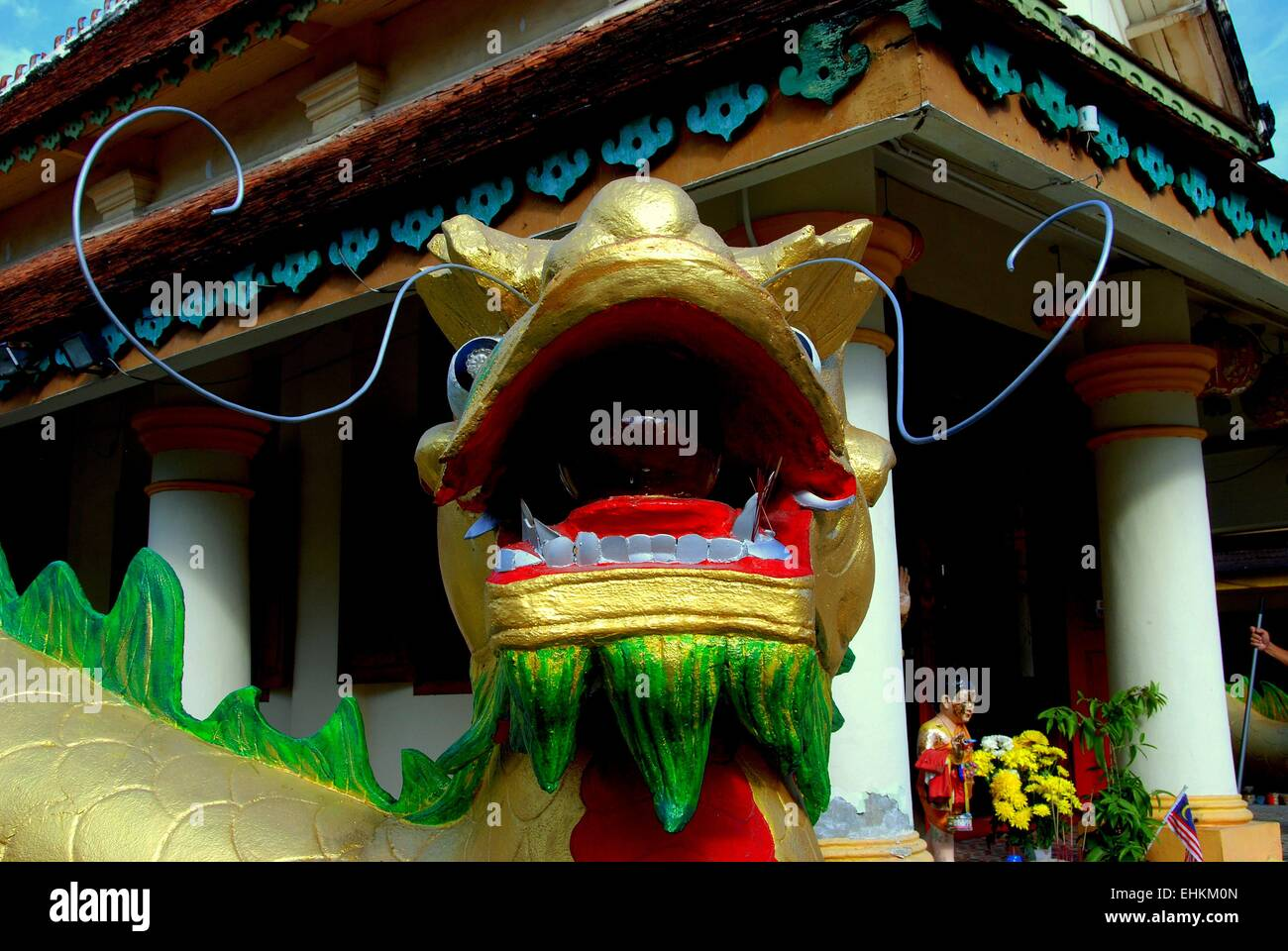 Georgetown, Malaysia: Closeup of an immense carved dragon with open mouth holding a symbolic ball at Thai Wat Buppharam Stock Photo