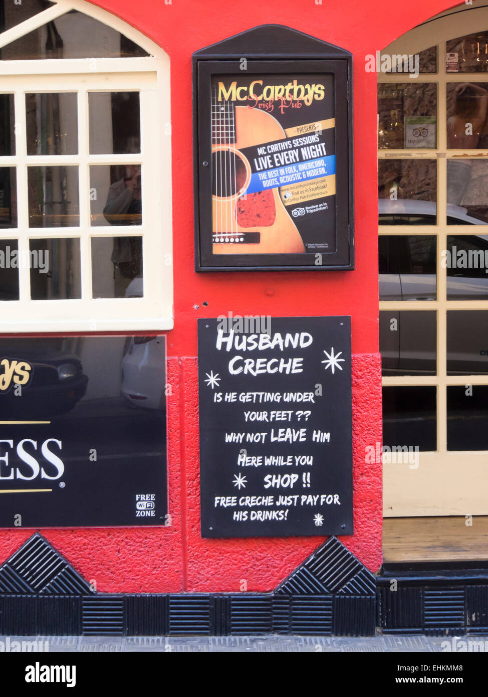 Irish bar in Corralejo Fuerteventura, Canary islands Spain, humorous sign about husbands and shopping - Stock Image
