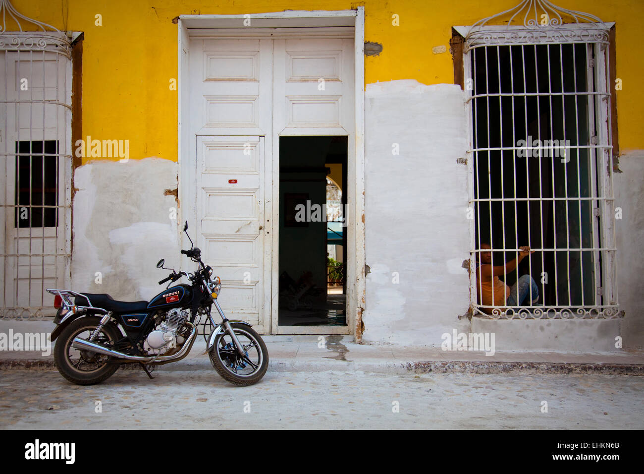 Moped in front of yellow wall, Trinidad, Cuba - Stock Image