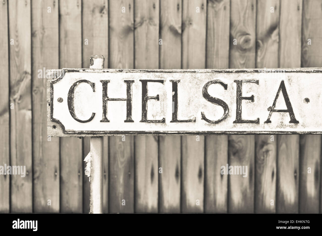 Chelsea road sign in front of a wooden fence in sepia tones - Stock Image