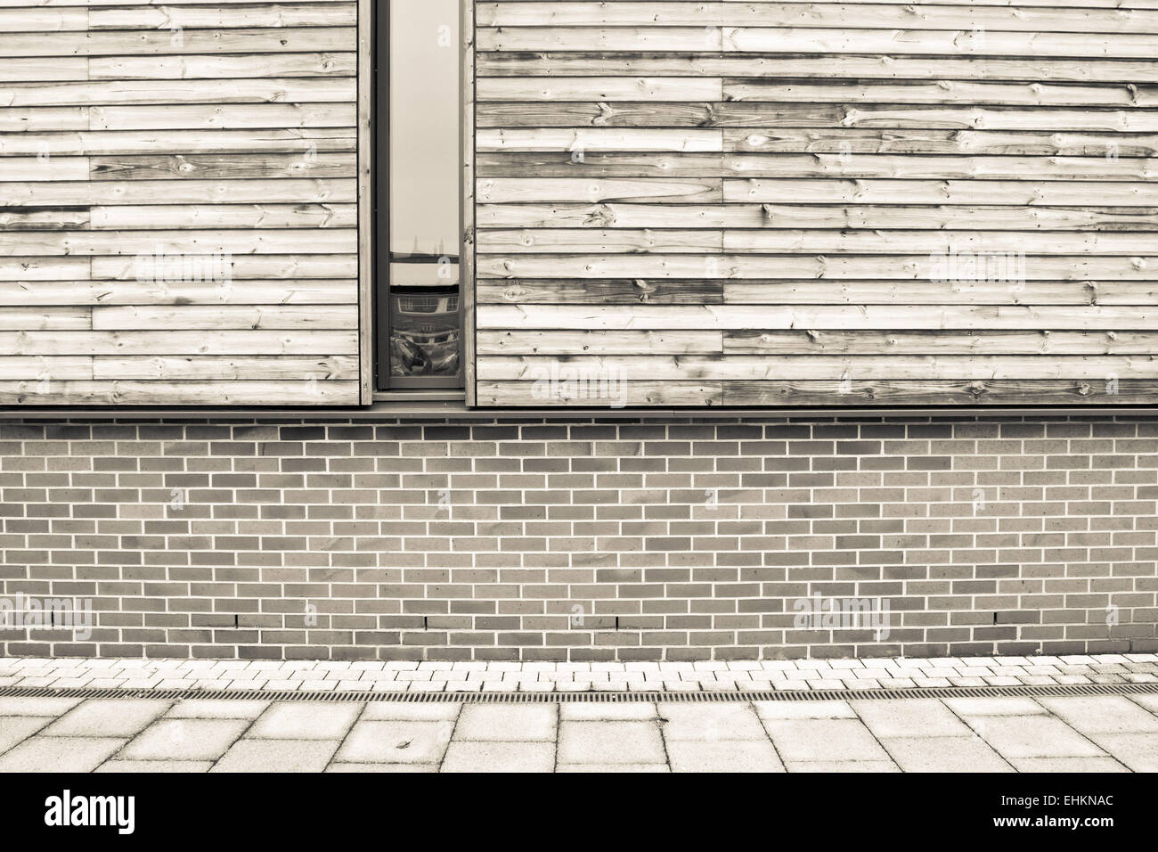 Brick and wooden wall on a modern eco building in sepia tones - Stock Image