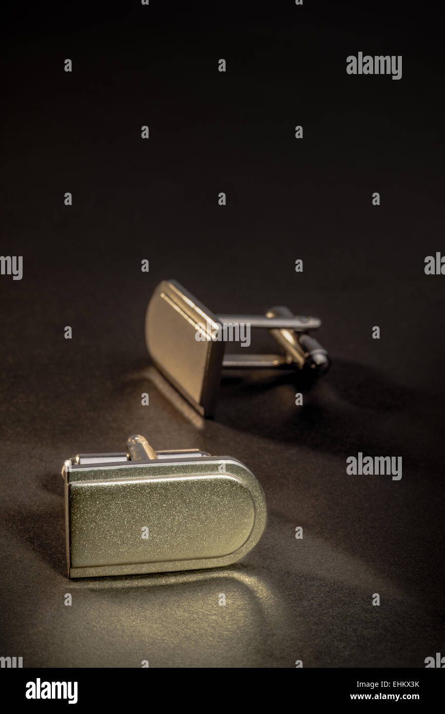 A pair of cuff-links on a dark counter top. - Stock Image