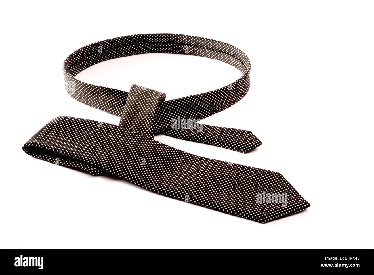 A black and white tie on a white isolated background in the process of being tied. - Stock Image