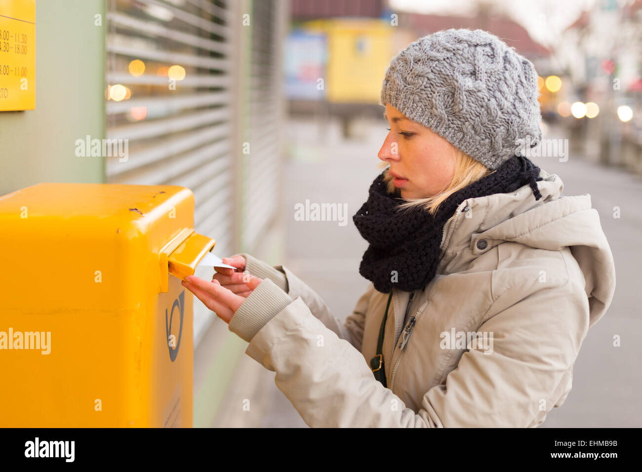 Young lady posting letters. - Stock Image
