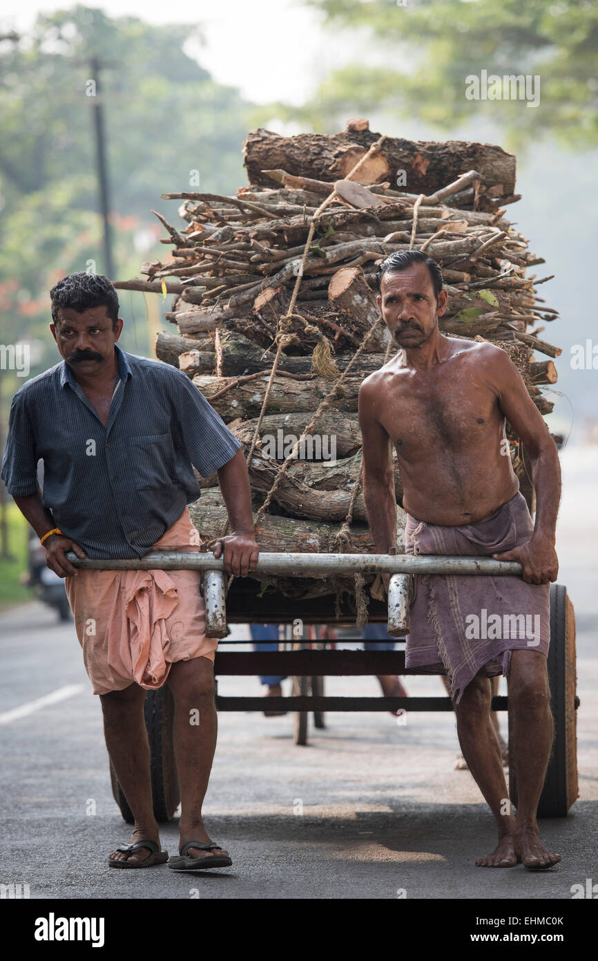 Day labourers pulling a cart laden with wood, Alappuzha, Kerala, India - Stock Image