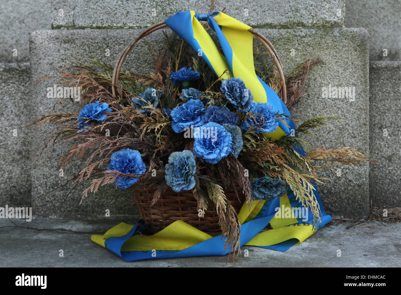 Blue flowers in a basket decorated with Ukrainian national flags at a military cemetery in Jablonne v Podjestedi, - Stock Image