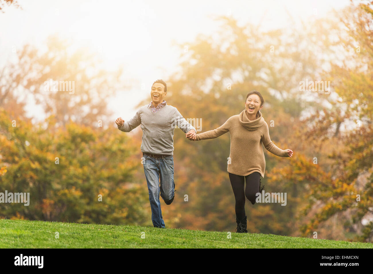 Smiling couple running in park Stock Photo
