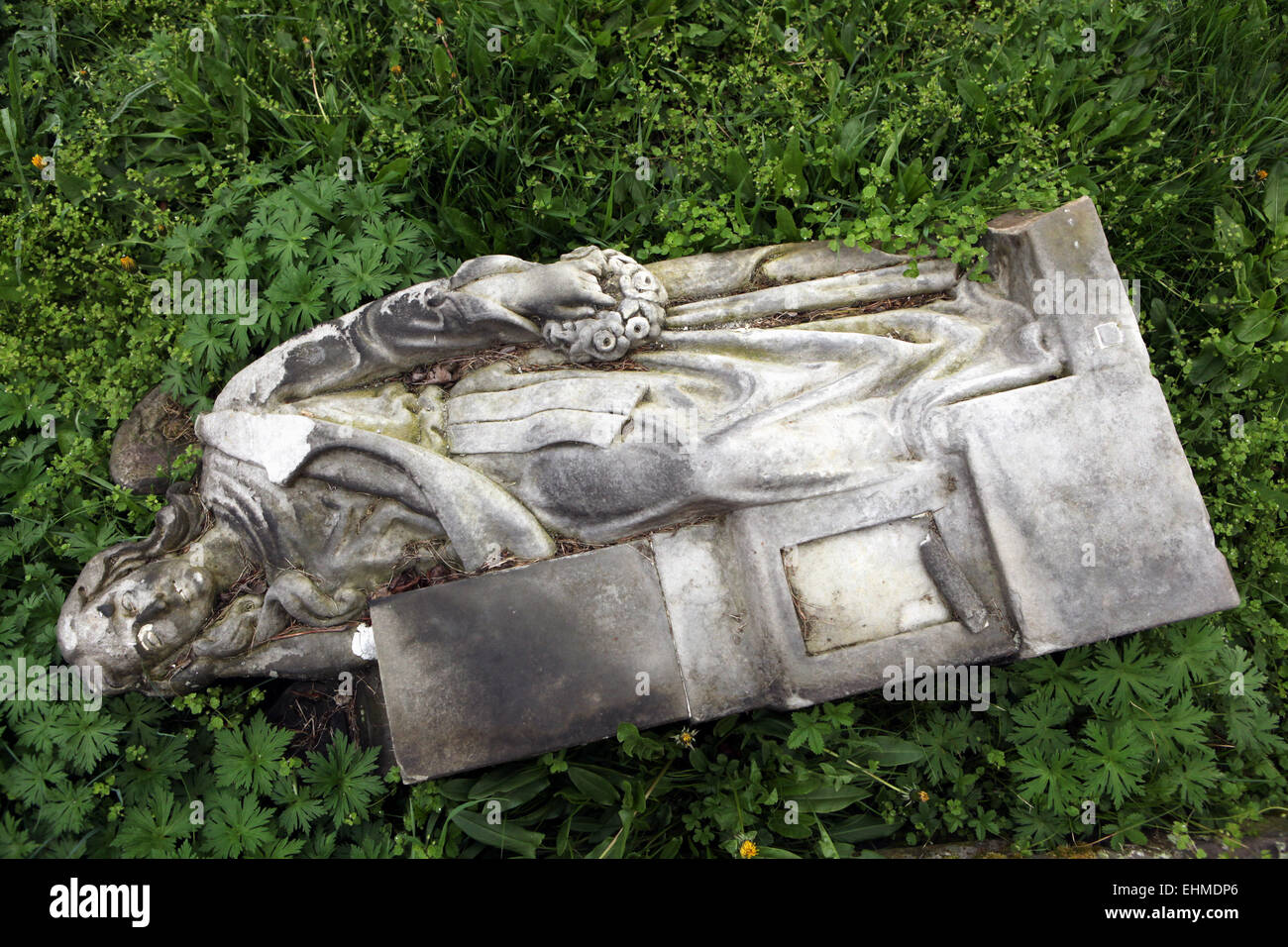 Fallen angel. Destroyed tombstone at an abandoned cemetery in Terezin, Czech Republic. - Stock Image