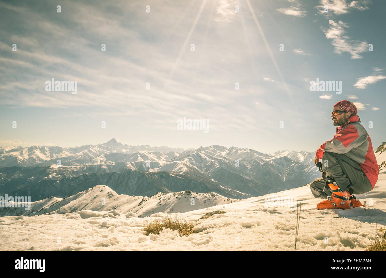 Alpinist on the mountain summit. Shot in backlight, stunning panoramic view of the alpine arc. Concept of success - Stock Image