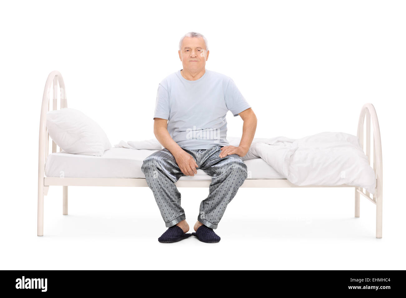 4d35be84f6 Senior man in pajamas sitting on a bed isolated on white background ...