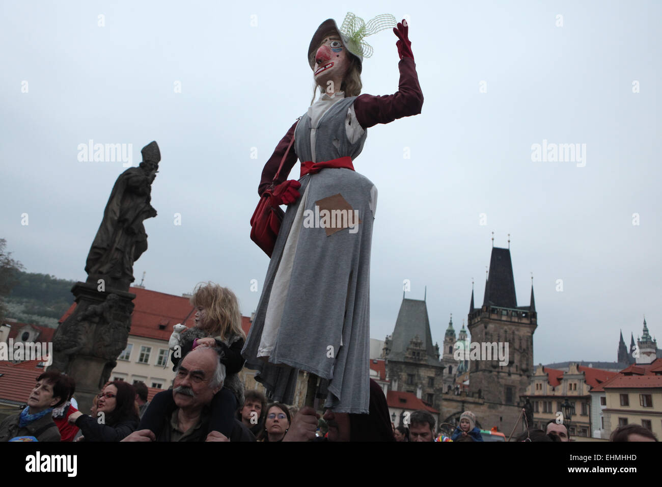 Participants of the costumed parade at the Witches Night carry a straw witch over the Charles Bridge in Prague, - Stock Image