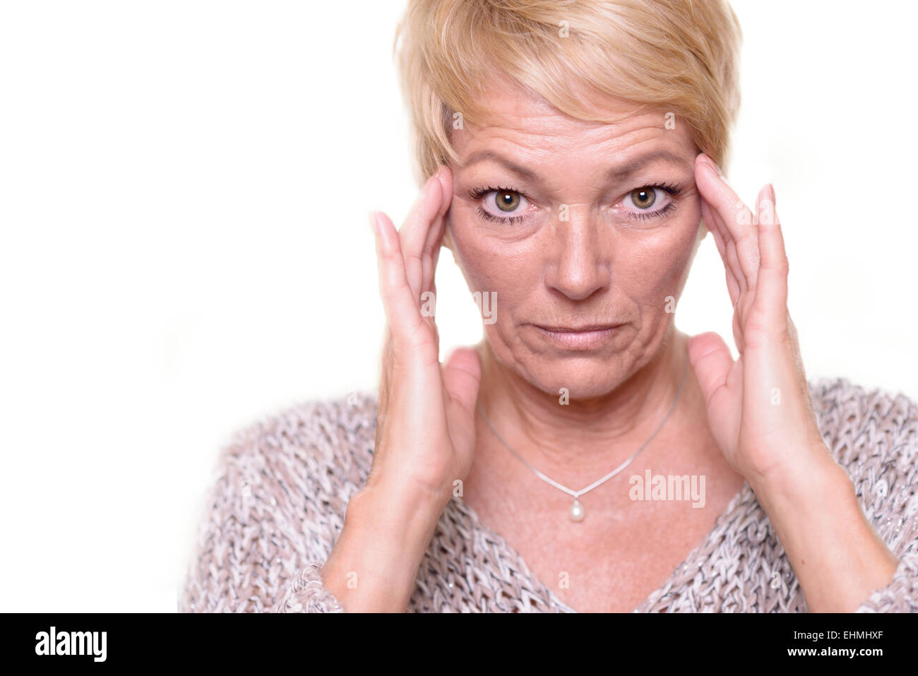 Attractive senior blond woman with a wide-eyed expression and her glasses on her head indicating headache or migraine - Stock Image