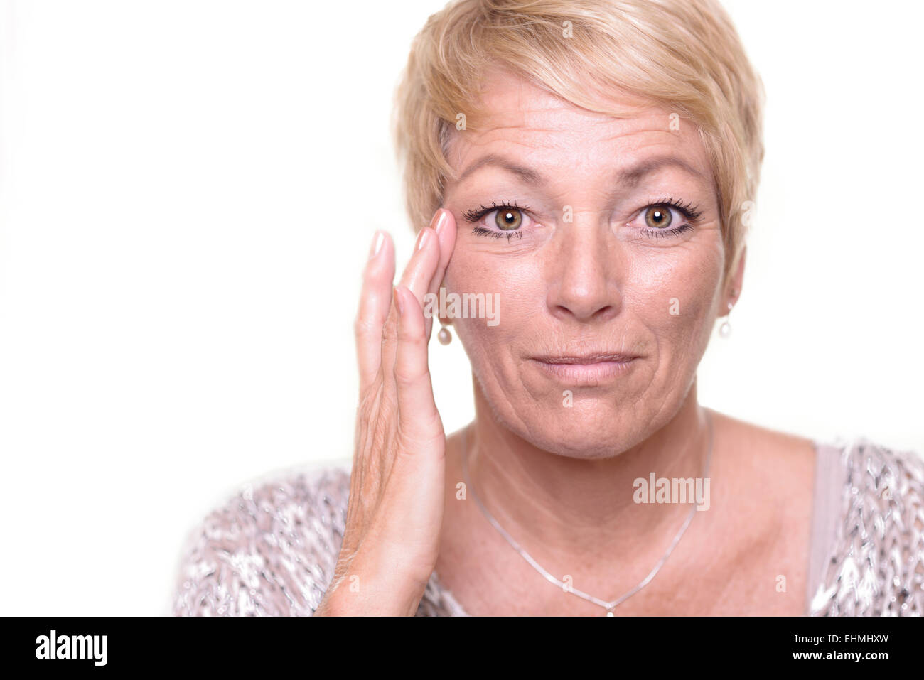 Attractive senior blond woman with a wide-eyed expression and her glasses on her head checking her complexion - Stock Image
