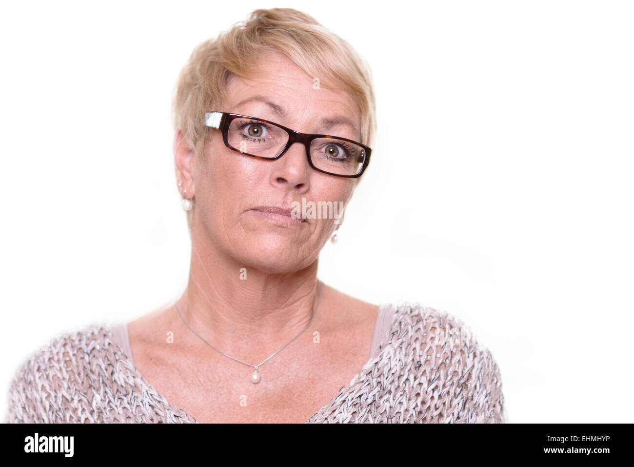 Distrustful stern middle-aged woman wearing glasses with a serious unyielding expression looking intently at the - Stock Image