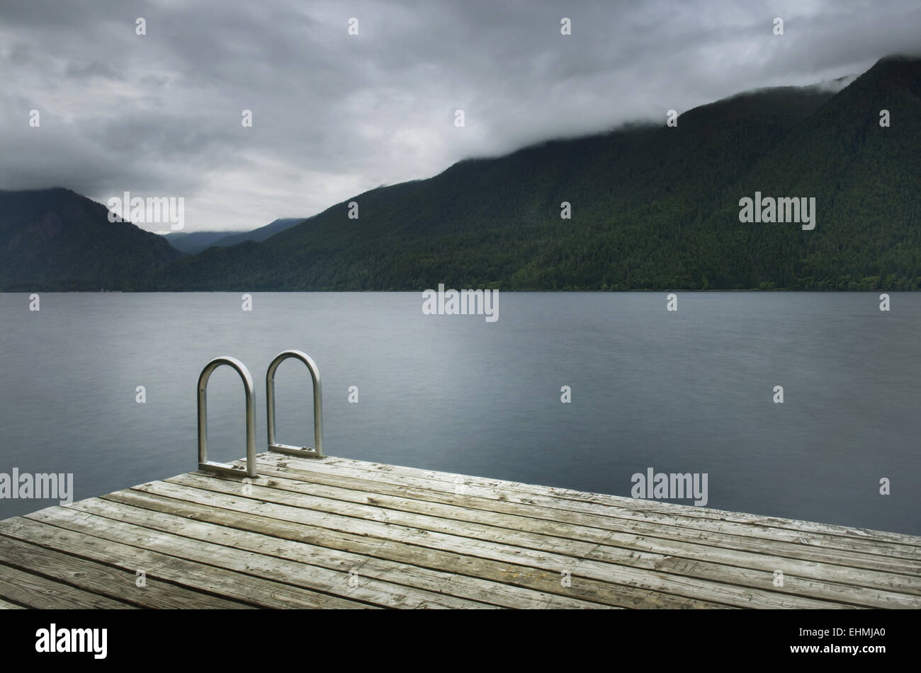 Ladder on wooden pier at still remote lake - Stock Image