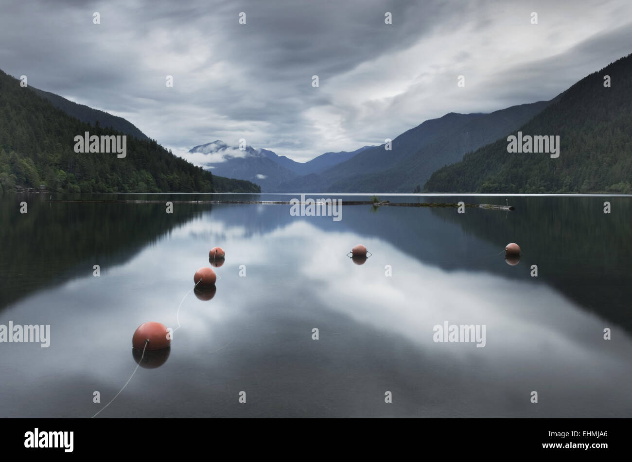 Buoys floating in still remote lake under clouds - Stock Image