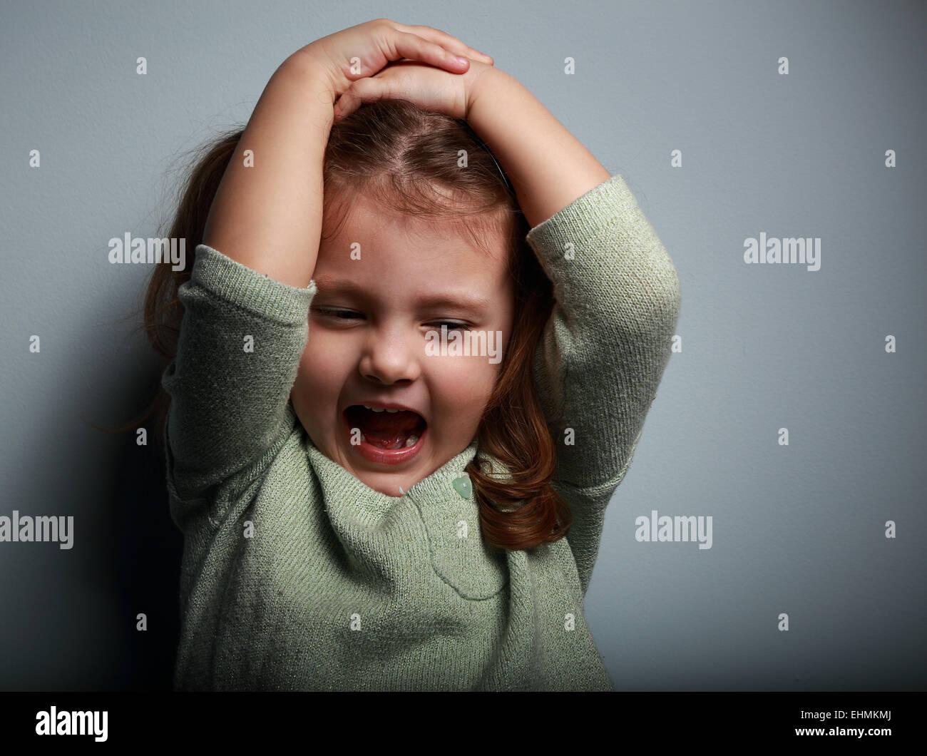 Angry kid girl shouting with open mouth and holding hands the head on dark background - Stock Image
