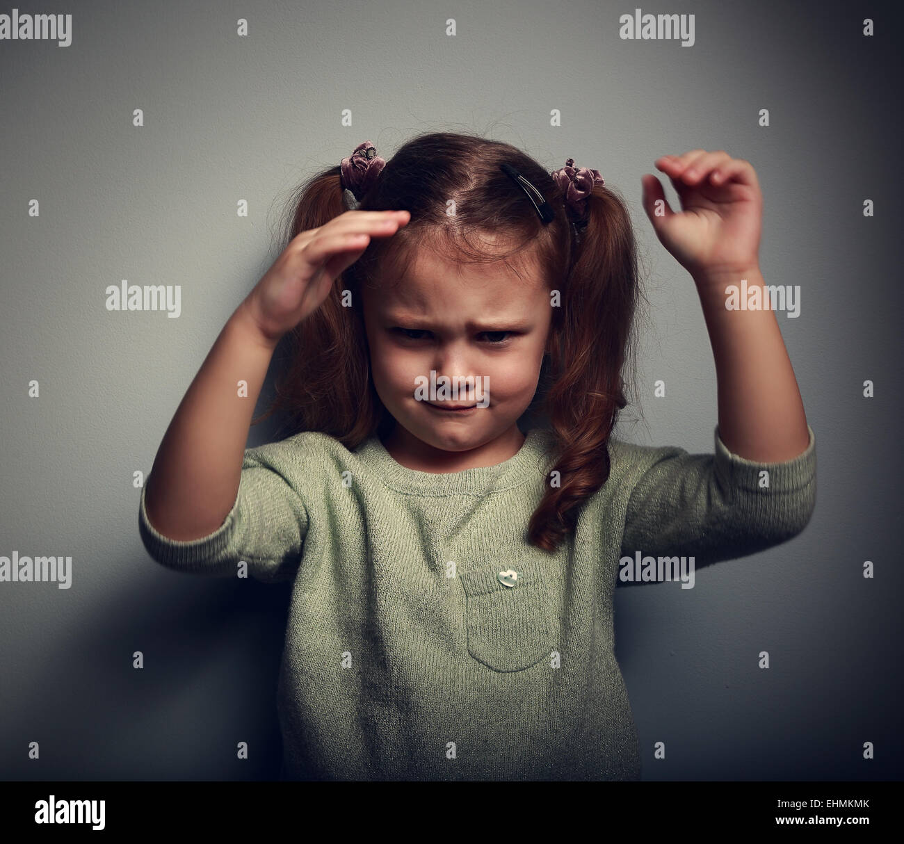 Very angry kid girl looking aggressive and waving the arms on dark background. Closeup portrait - Stock Image