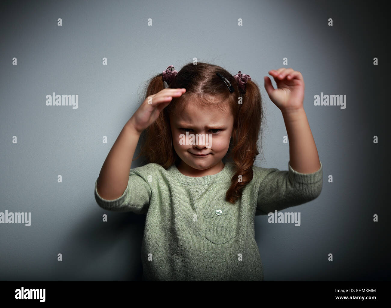 Angry kid girl moving the hands on dark background - Stock Image