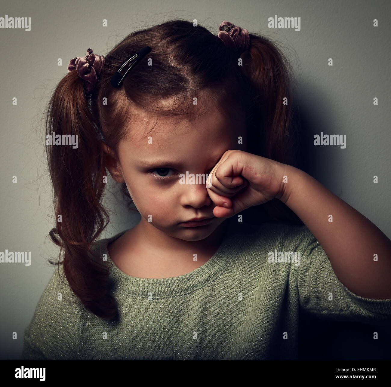 Unhappy crying kid girl in darkness. Closeup vintage portrait - Stock Image