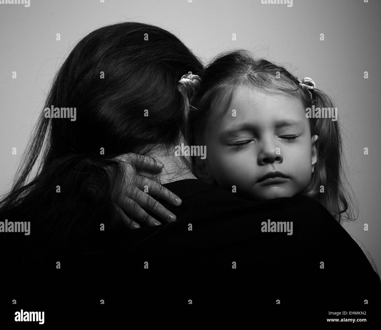 Depression daughter hugging her mother with sad face. Closeup portrait black and white - Stock Image