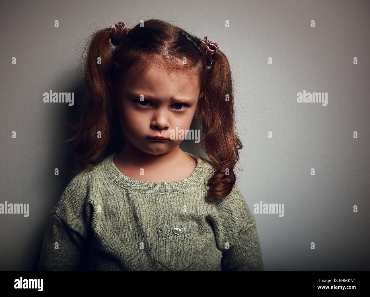 Sad kid girl with long hair looking. Closeup vintage portrait - Stock Image