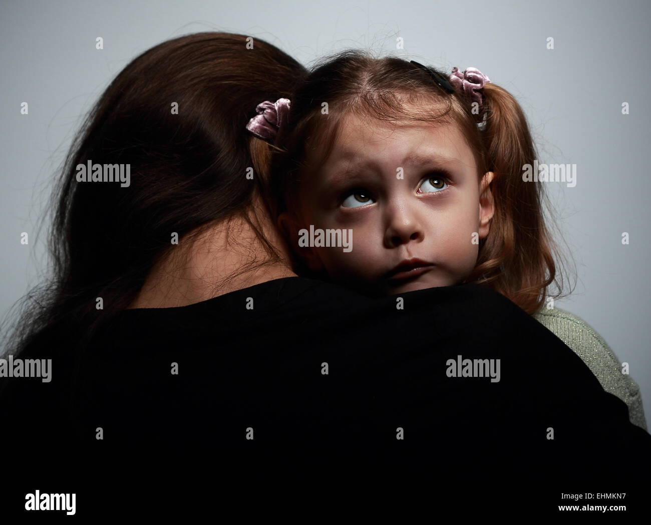 Thinking sad daughter embracing her mother and looking up on dark background - Stock Image
