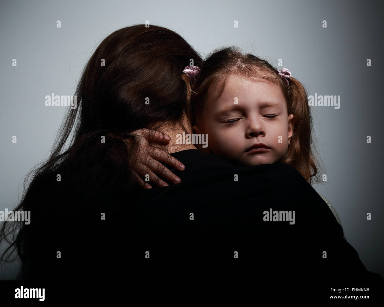 Sad crying daughter hugging her mother with sad face on dark shadows background - Stock Image
