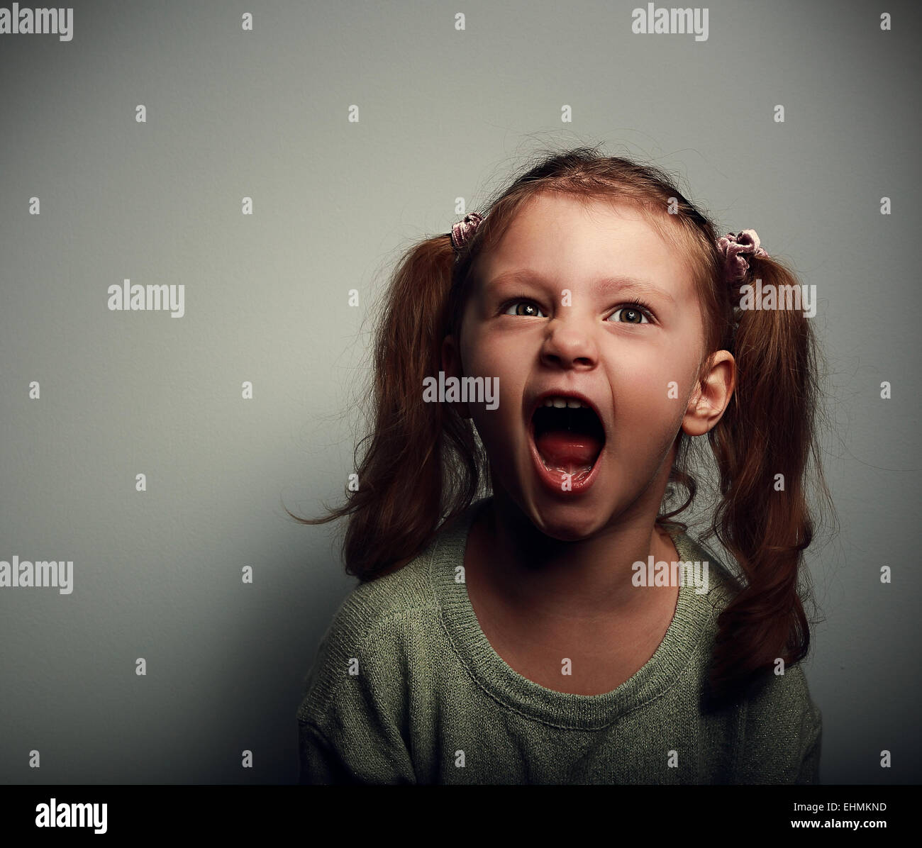 Shouting angry kid girl with open mouth and negative look on dark background - Stock Image