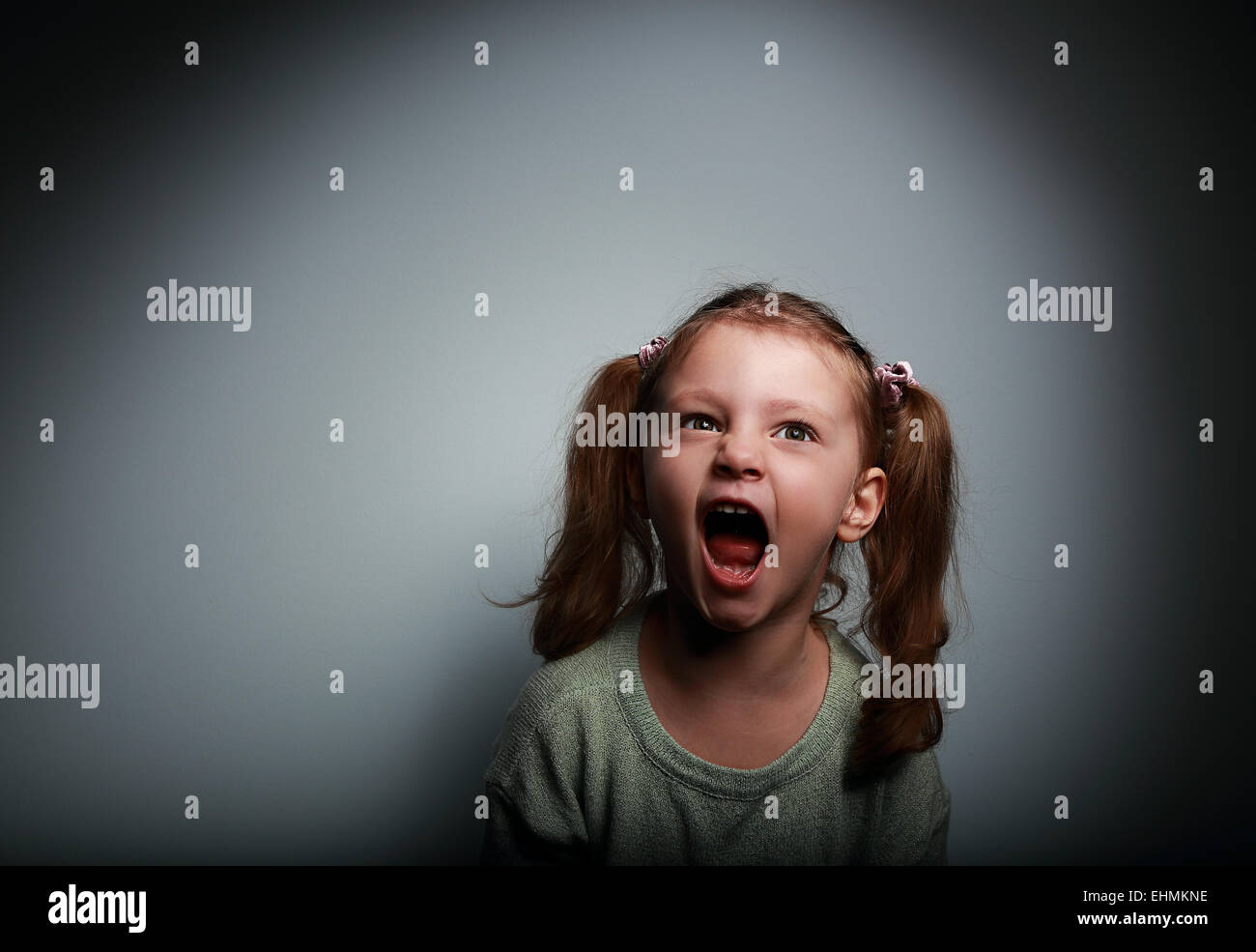 Angry child girl screaming with opened mouth and looking up with evil on dark background - Stock Image