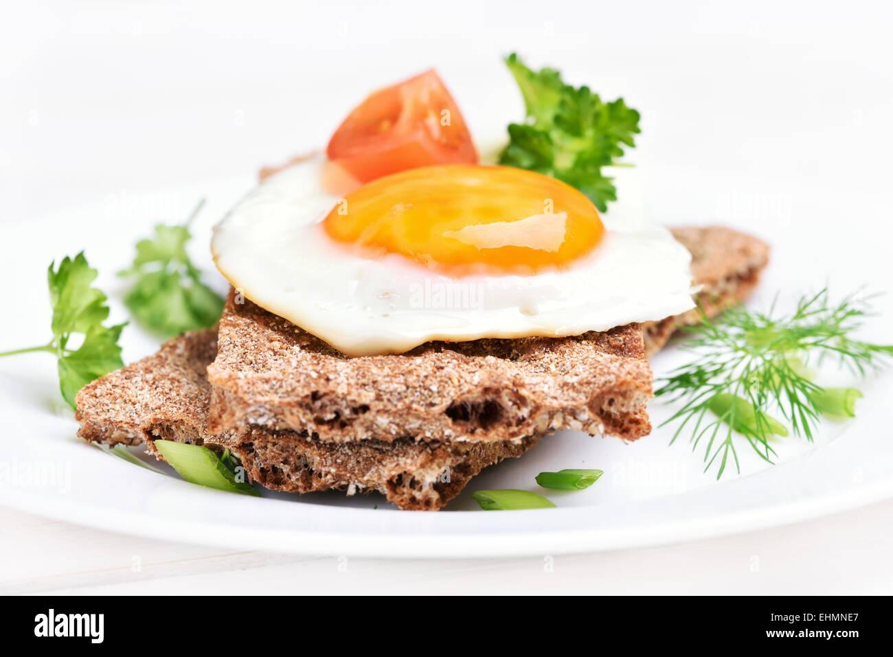 Breakfast fried egg on crispbread, close up view - Stock Image