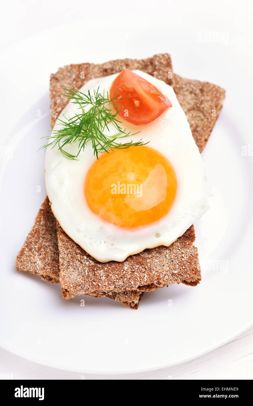 Fried egg, dill and tomato slice on crispbread, top view - Stock Image
